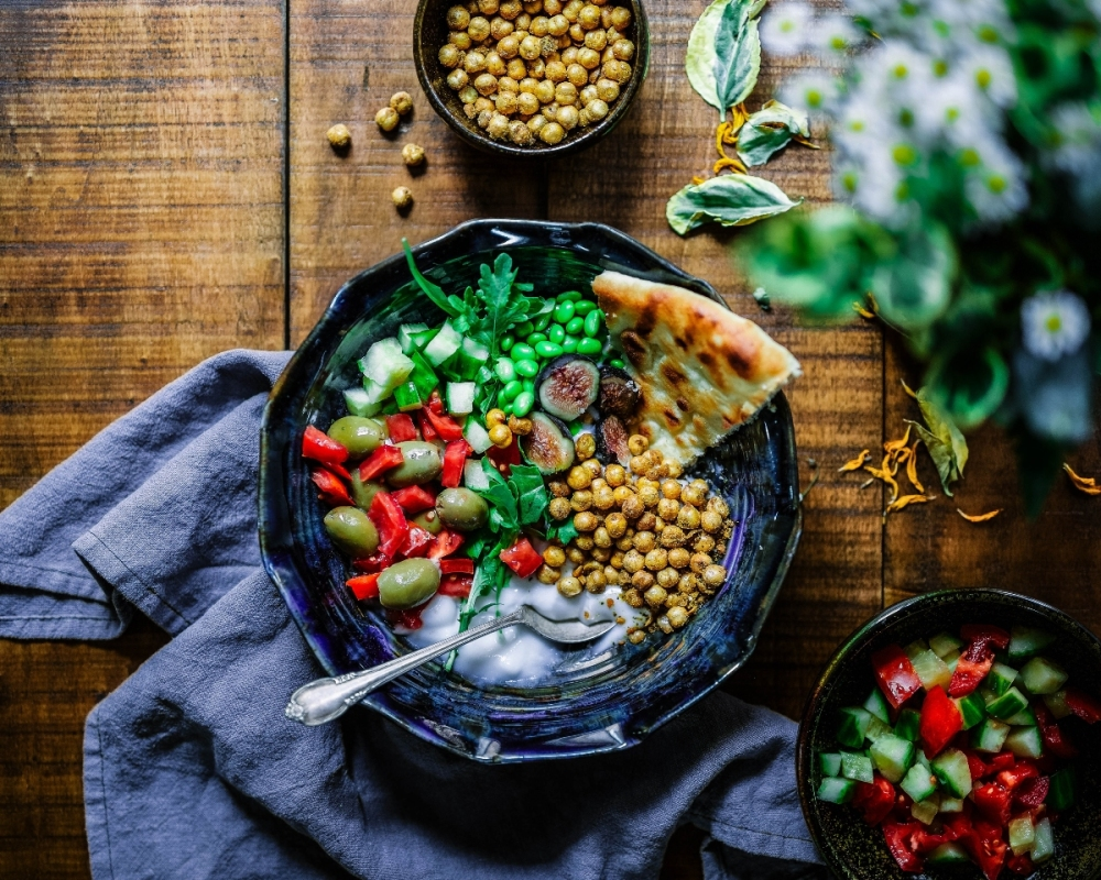 Plant-based food including olives, chickpeas, salad and flatbread presented attractively in a bowl on a wooden table