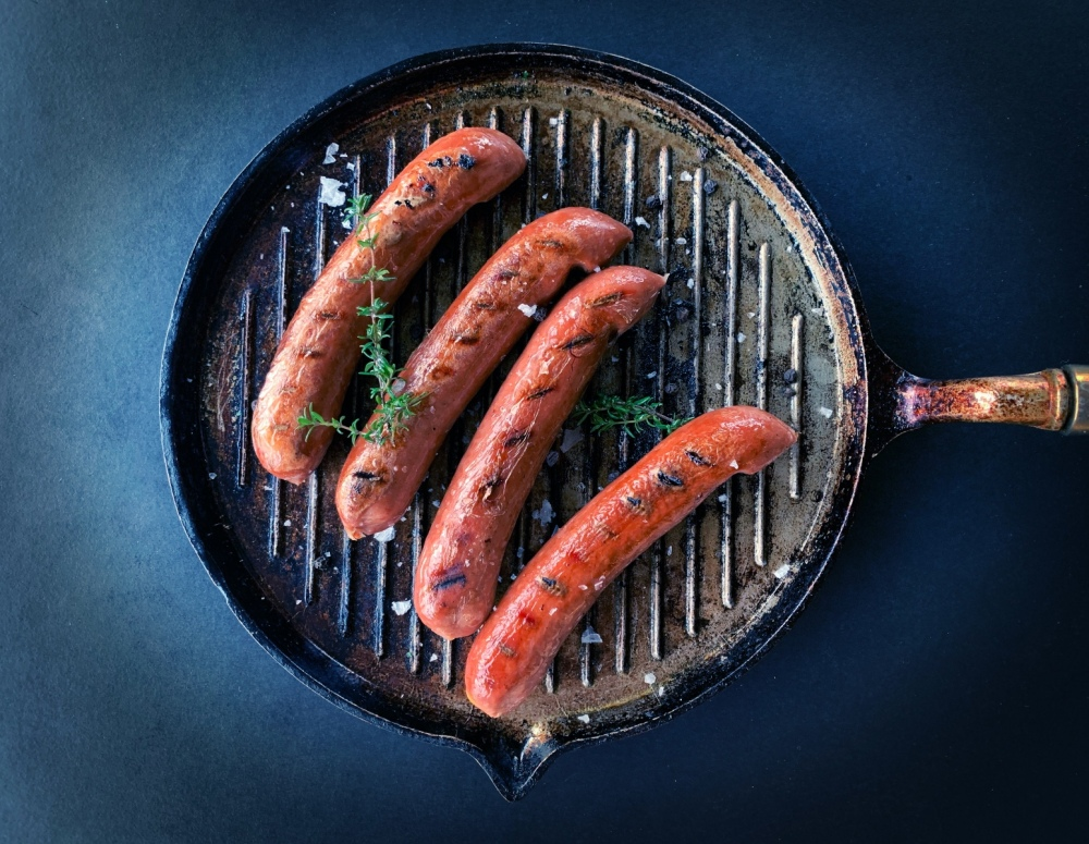 Plant-based sausages sizzling in a frying pan with some herbs