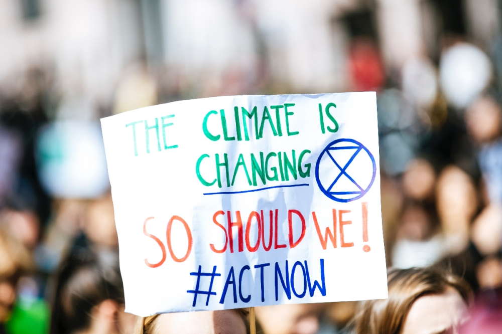 Protest placard saying the climate is changing, so should we with the hashtag act now