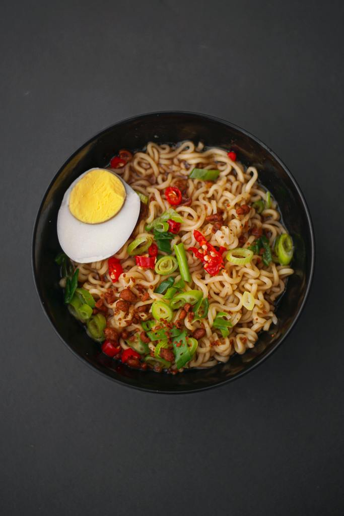 Photo of mushroom ramen noodles with red chili, spring onions and an egg on top
