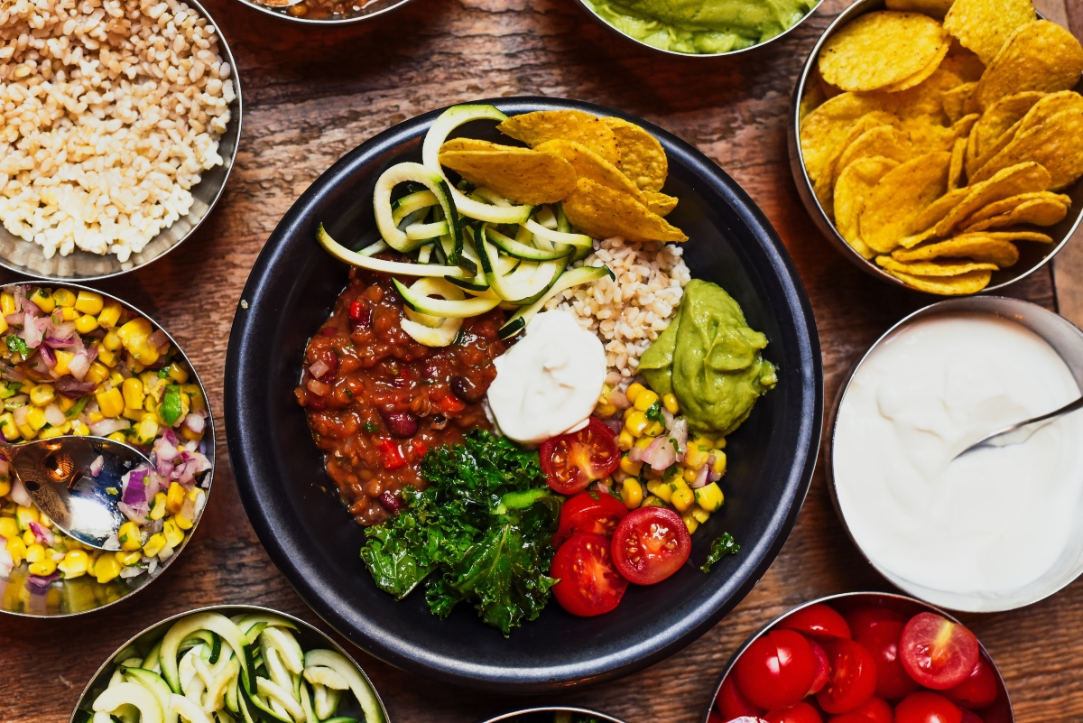 Plant-based chilli spread, including tortilla chips, sour cream, guacamole, tomatoes and sweetwcorn